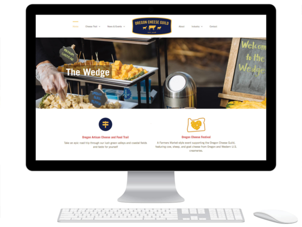 Desktop computer displaying the homepage of the Oregon Cheese Guild website