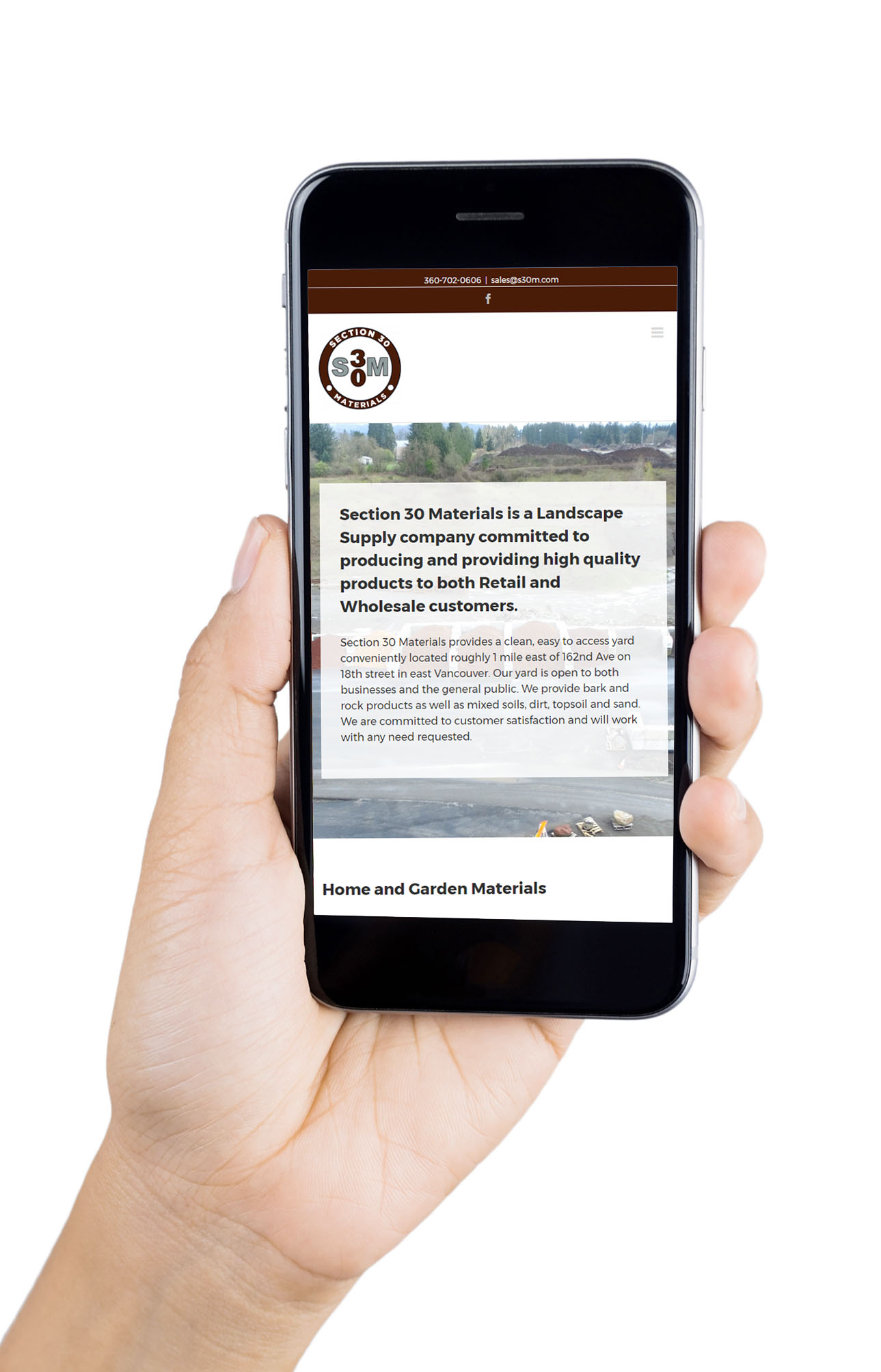 Hand holding a smart phone, showing how the S30M website looks on mobile.